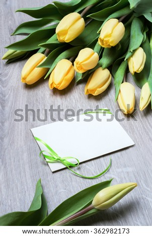 Design for Anniversary, Birthday, Mothers Day or Easter celebration. Yellow tulips and a blank greeting card on wooden table. This image is toned. - stock photo