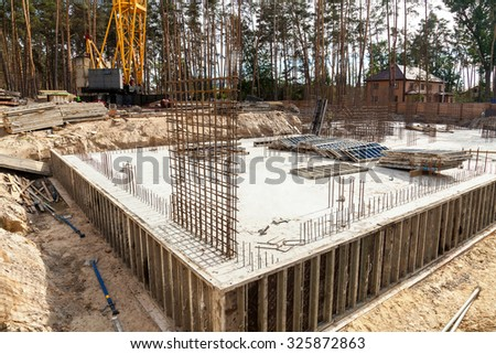 Design of reinforcement cage of reinforcement for concrete frame house, brick house, formwork for concrete pouring, construction site, working crane, construction of houses - stock photo