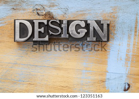 design word in vintage letterpress metal type blocks on wood surface with grunge blue paint - stock photo