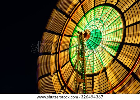Designed by George Washington Gale Ferris, Jr.  The Ferris wheel is the most common type of amusement ride at state fairs in the United States. This is a long exposure showing the motion of the ride. - stock photo