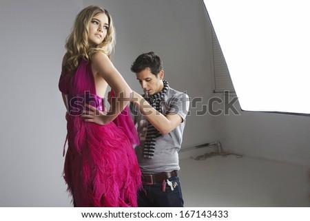 Designer adjusting dress on fashion model in studio - stock photo
