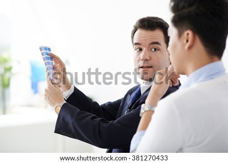 Designer and client choosing color for logo - stock photo