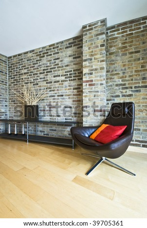 designer armchair with cushion on a brick wall back round - stock photo