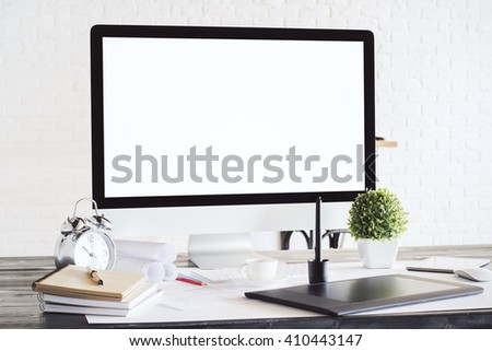 Designer desktop with blank white computer screen, graphic tablet, alarm clock and other items. White brick background. Mock up - stock photo