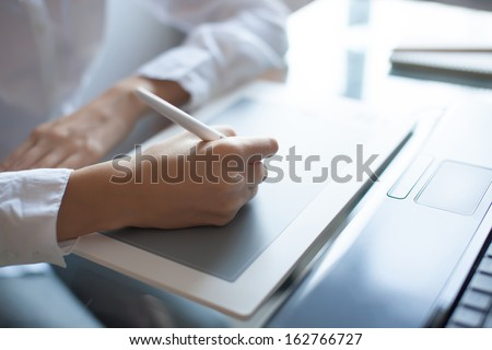 Designer girl drawing with graphics pad - stock photo