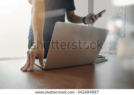 designer hand working and smart phone and laptop on wooden desk in office  - stock photo