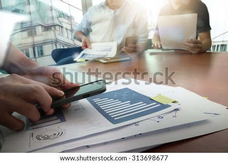 designer hand working and smart phone and laptop on wooden desk in office and two colleagues discussing data with london city background