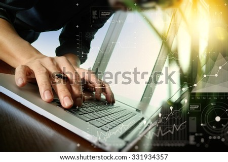 designer hand working with laptop and business digital layer diagram with green plant foreground on wooden desk in office - stock photo