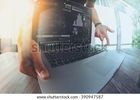 Designer hand working with laptop computer on wooden desk as responsive web design concept - stock photo