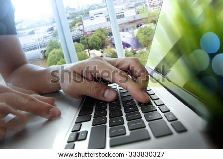 designer hand working with laptop computer with green plant foreground on wooden desk in office - stock photo
