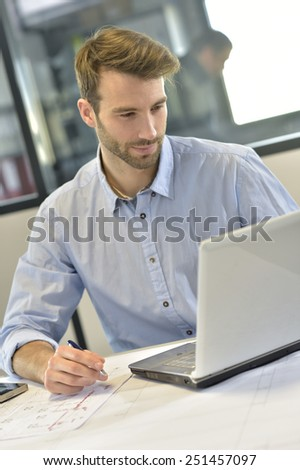 Designer in office working on project with laptop - stock photo