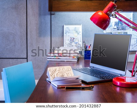 Designer modern home office desk with laptop and equipment - stock photo