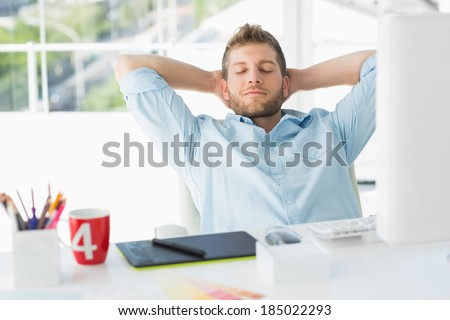 Designer relaxing at his desk in creative office - stock photo