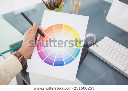 Designer working at desk using a colour wheel in his office - stock photo