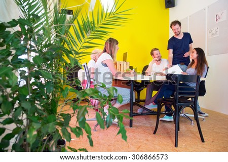 Designers, sitting in at a large table in a creative environment and office, surrounded by tack boards with drawings, plants and a bright yellow wall - stock photo