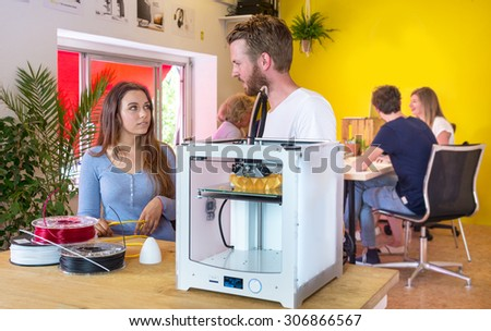 Designers standing behind a 3D printer, surrounded with coils of biodegradable polymer, waiting for a product concept to be printed in the printer. Other engineers working togegher in the background - stock photo
