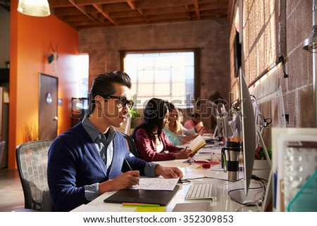 Designers Working At Desks In Modern Office - stock photo