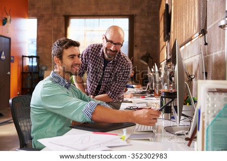 Designers Working Together At Desks In Modern Office - stock photo