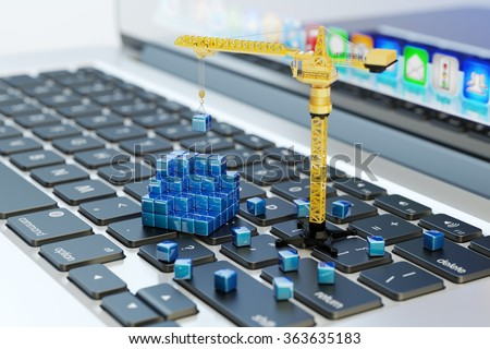 Designing, engineering, business planning and project development, computer technology concept, construction crane on laptop keyboard assembles abstract blue blocks - stock photo