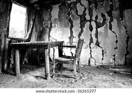 Desk and chair in abandoned cabin - stock photo