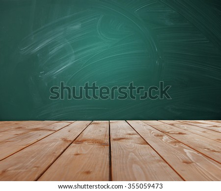 Desk and chalkboard - school background - stock photo
