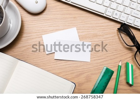 Desk. Blank business cards with supplies and coffee cup on wooden office table - stock photo