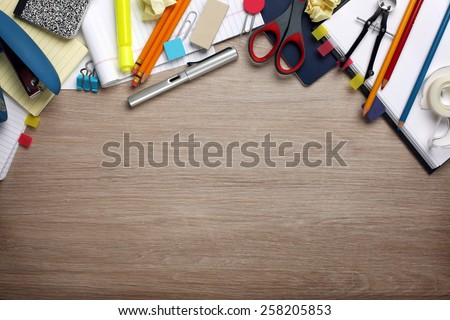 Desk cluttered with office supplies - stock photo