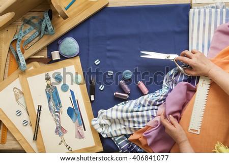Desk designer fashion. Fashion designer starts cutting fabric to create fashionable clothes on the sketches. - stock photo