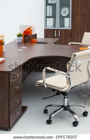 desk, leather chair and bookcase on a white wall - stock photo