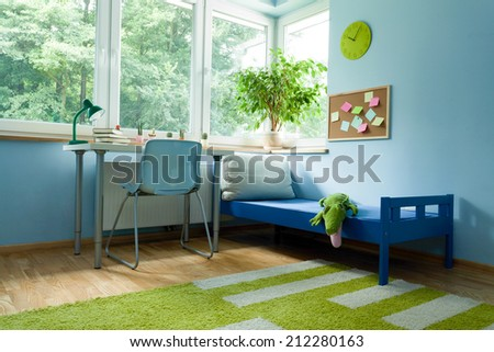 Desk near to boy bed in his room - stock photo