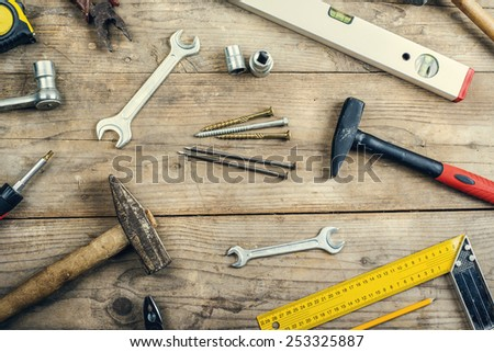 Desk of a carpenter with different tools. Studio shot on a wooden background. - stock photo