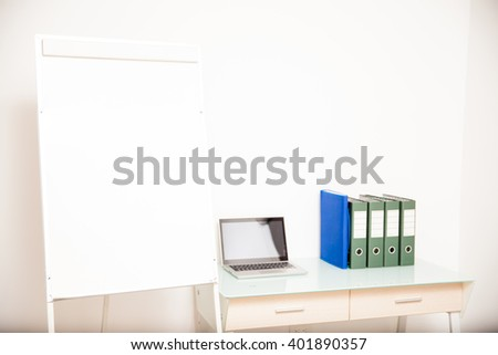 Desk of a teacher with a laptop computer, some documents and a blank flip chart with lots of copy space - stock photo