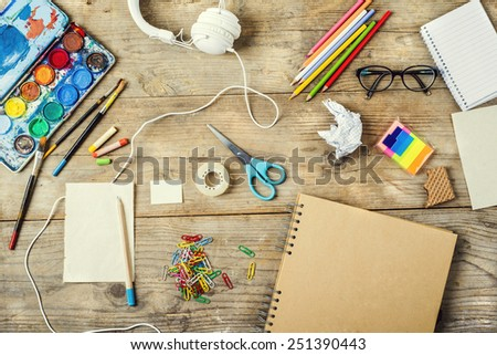 Desk of an artist with lots of stationery objects. Studio shot on wooden background. - stock photo