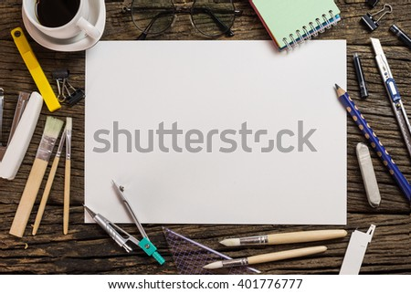 Desk of an artist with lots of stationery objects. Studio shot on wooden background,View from above. - stock photo