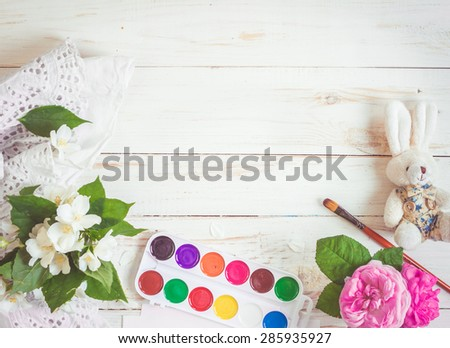 Desk of creative worker. Paints, brush and flowers. Top view background - stock photo