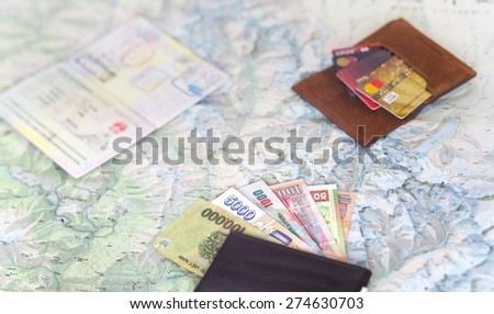 Desk of frequent traveler - angle view. The composition essential items for trip passport multiple entry stamps cash notes from different countries, wallet credit cards, detailed map on the background - stock photo