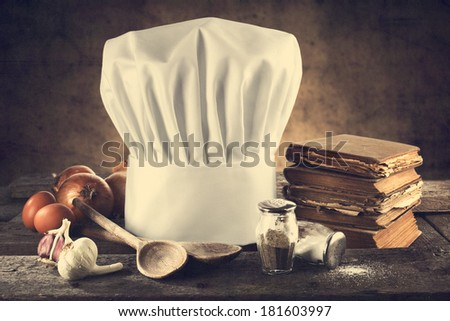 desk of wood wall and cook hat  - stock photo