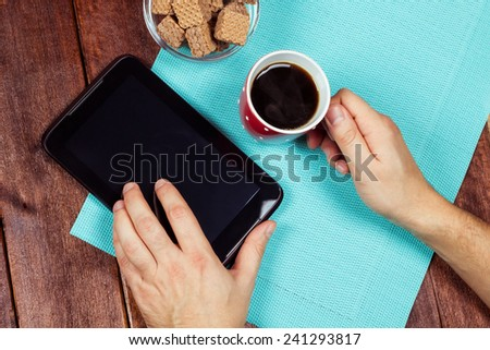 Desk office worker. A young man at work. Tablet PC on the desk. Cup of black coffee, men's hands, waffles, and the plate on the table. Top view. - stock photo