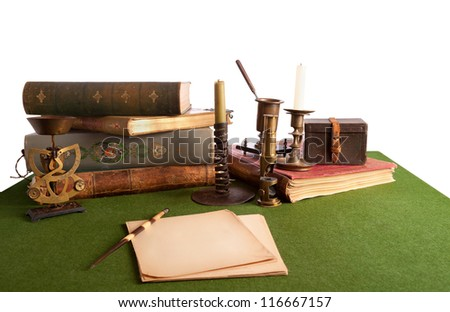 Desk with an open book and old stationery. Isolated on white. Books and pictures of pictures published from 1892 to 1896 years. - stock photo