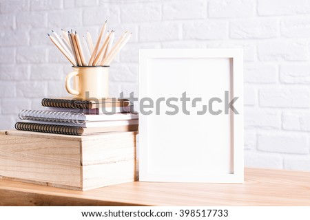 Desk with blank white picture frame and pencils in iron mug placed on books and wooden box. Mock up - stock photo