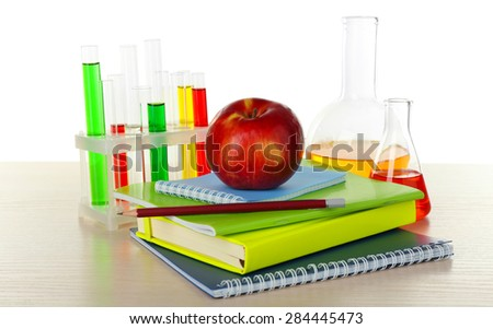 Desk with books and test tubes isolated on white - stock photo