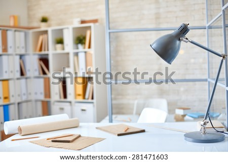 Desk with lamp, papers and pencils in office - stock photo