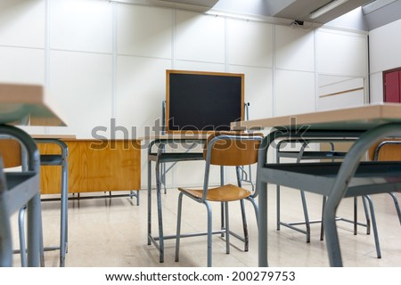 desks and blackboard in classroom at school - stock photo