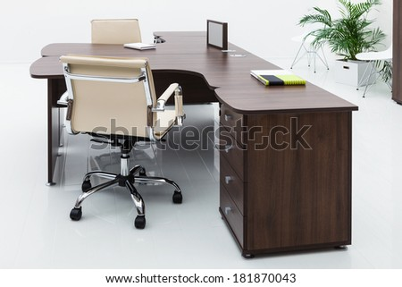 desks and leather chairs on a white wall - stock photo