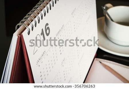 Desktop calendar sitting on desk showing year of 2016. Home office table with stationary calendar coffee paper pencil Happy New Year Start Life office Home Leap World Press Freedom Day concept. - stock photo