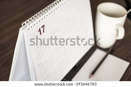 Desktop calendar sitting on desk showing year of 2017. Home office table with stationary, calendar, coffee, paper, pencil, January, Happy New Year, Beginning, Start, Life, office, Home concept. - stock photo