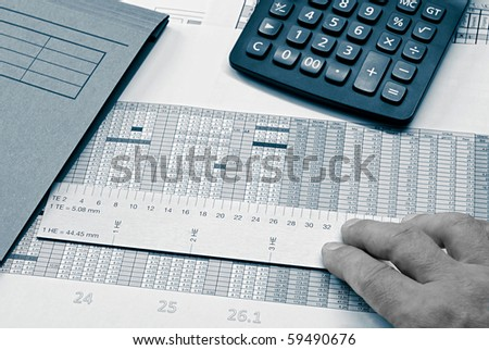 desktop - pen, ruler and calculator on a document - stock photo