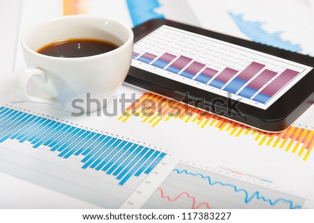 Desktop with lots of paperwork, tablet PC and a cup of fresh coffee. Business concept - stock photo