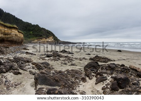 Desolate beach in the Central Oregon coast with its typical grey skies and dramatic changes in the landscape - stock photo