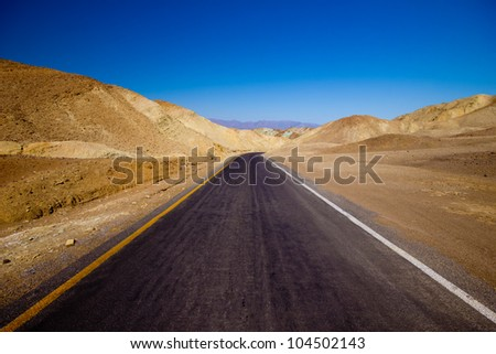 Desolate desert road in Death Valley National Park, California - stock photo